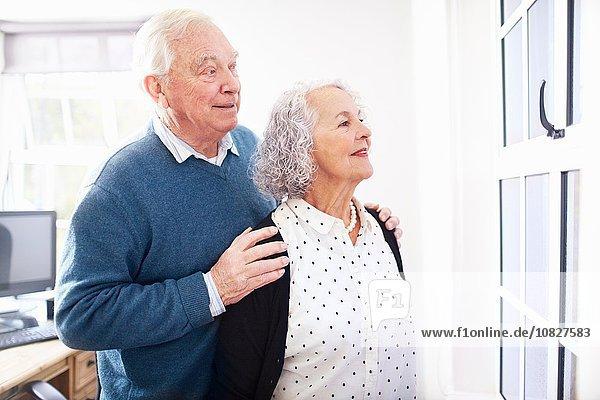Seniorenpaar im Büro lächelnd aus dem Fenster schauend