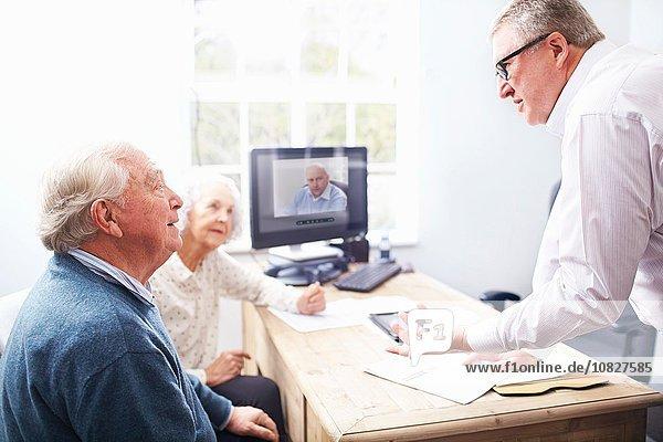Geschäftsmann im Amt im Gespräch mit einem älteren Ehepaar