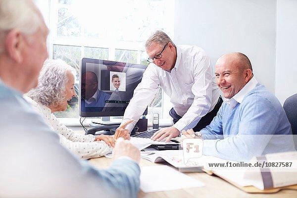 Geschäftsmänner im Amt im Gespräch mit einem älteren Ehepaar