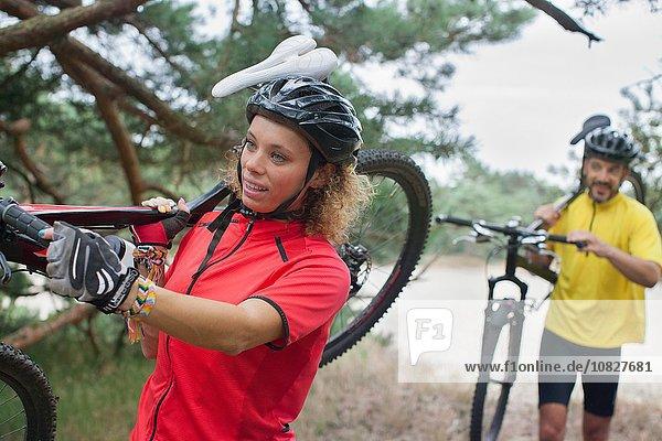 Mountainbike-Paar mit Fahrrädern über Sand am Flussufer