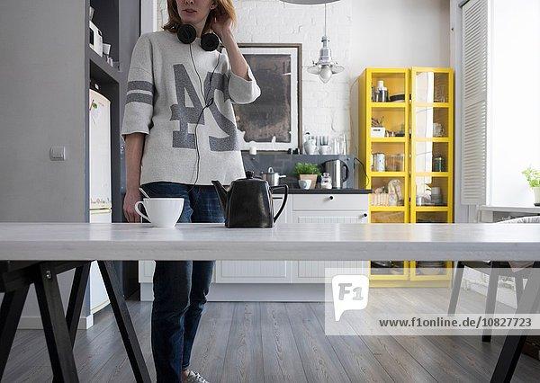Mittlere erwachsene Frau mit Kopfhörern um den Hals am Küchentisch