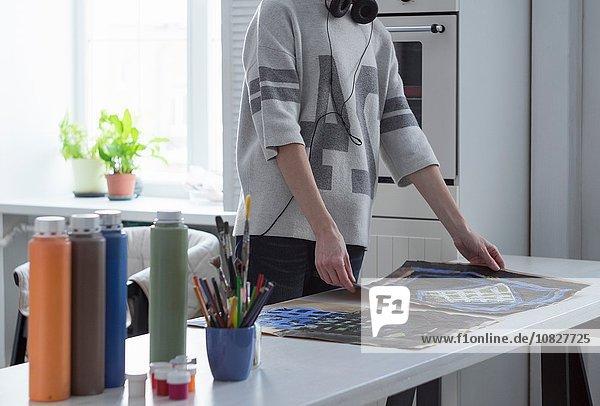 Künstlerin beim Malen am Küchentisch