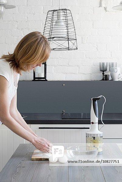 Frau beim Backen mit Mehl und Eiern am Küchentisch