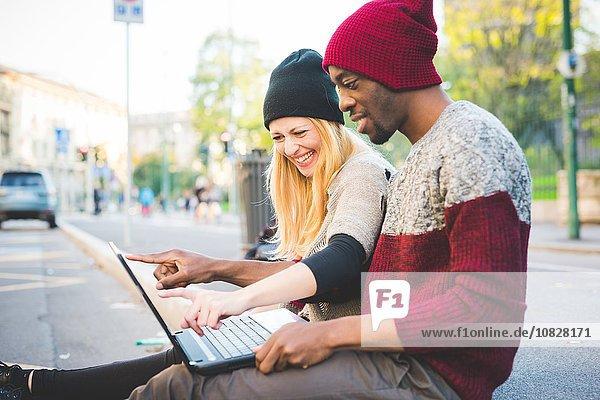 Paar mit Laptop auf dem Bürgersteig