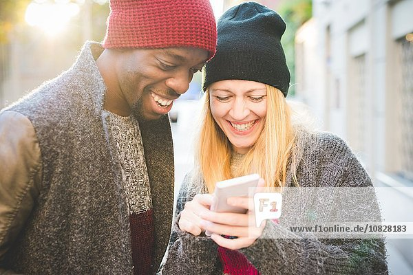 Paar lächelt auf Nachricht auf dem Smartphone