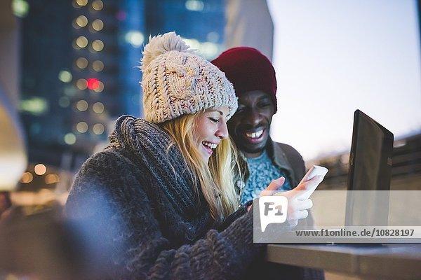 Paar mit Smartphone und Laptop im Freien in der Abenddämmerung