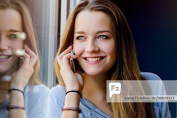 Junge Frau  die sich gegen das Fenster lehnt  telefoniert und lächelnd wegschaut.