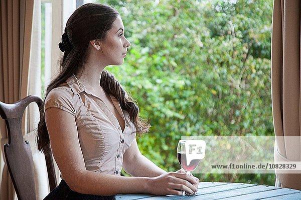 Junge Frau sitzt am Tisch vor dem Fenster und hält ein Glas Wein.