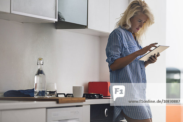 Woman using digital tablet in kitchen