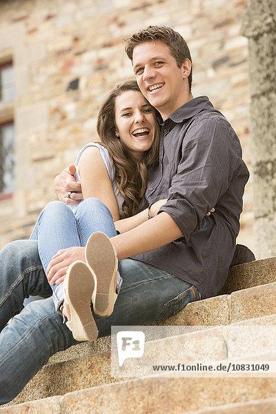 Caucasian couple sitting on castle steps