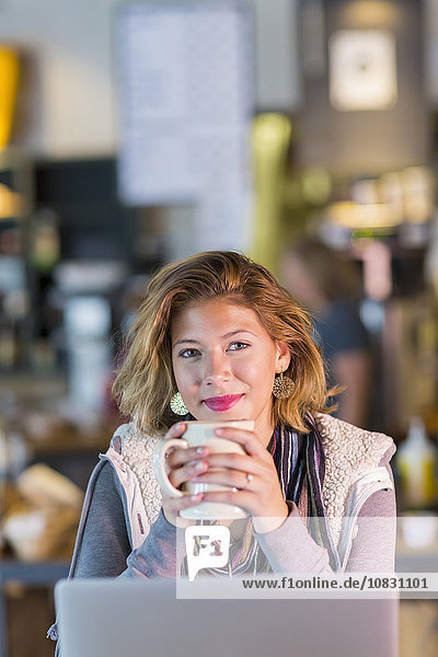 Mixed race teenage girl drinking cup of coffee