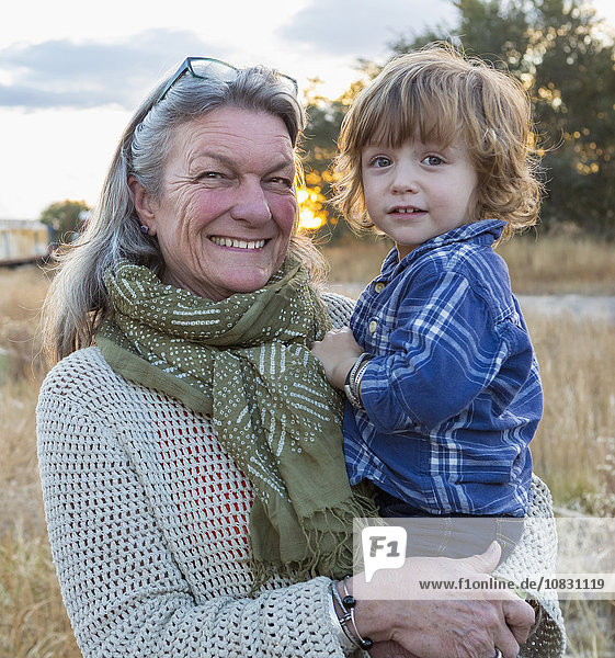 Caucasian grandmother holding grandson outdoors