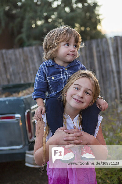 Caucasian girl carrying brother on shoulders