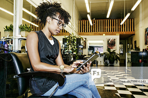 Mixed race hairstylist using digital tablet in salon