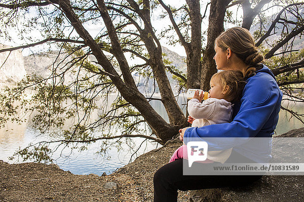 Caucasian mother and daughter sitting at lake