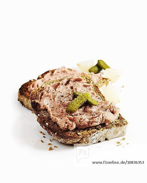 Getoastete Brotscheibe mit Hähnchenleberpastete und Essiggurken