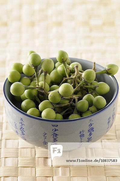 Grüne Thaiauberginen in Keramikschüssel