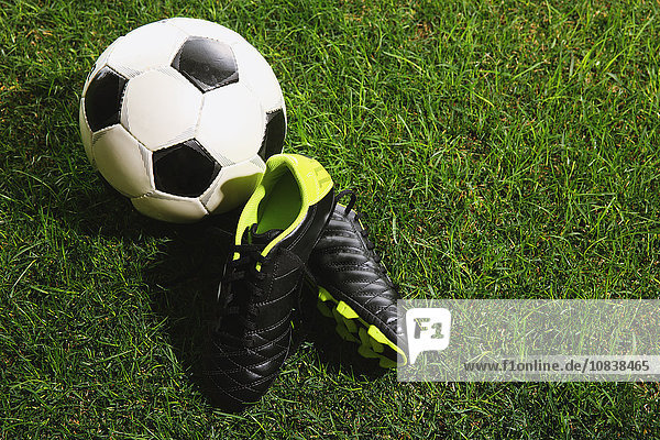 Soccer ball and shoes on grass
