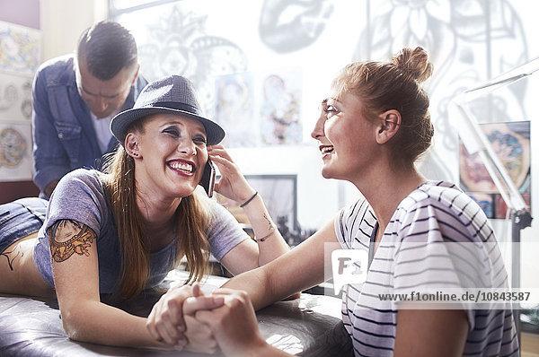 Lächelnde Frau mit Freundin beim Tätowieren