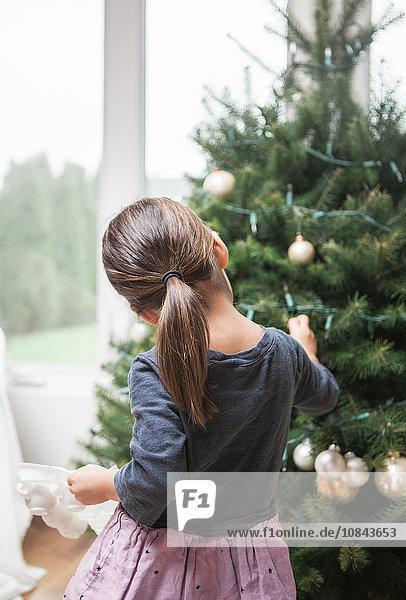 Kleinkind Mädchen schmückt Weihnachtsbaum