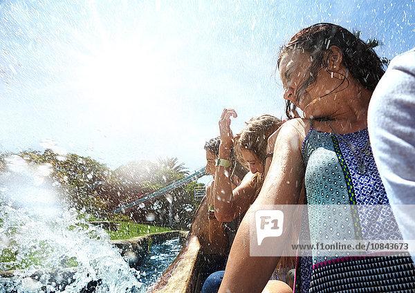 Junge Frauen werden beim Wasserparkfahren bespritzt