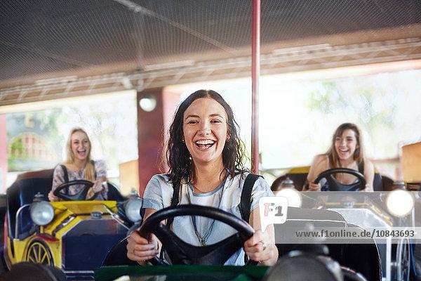 Porträt einer lächelnden jungen Frau  die im Vergnügungspark Auto fährt