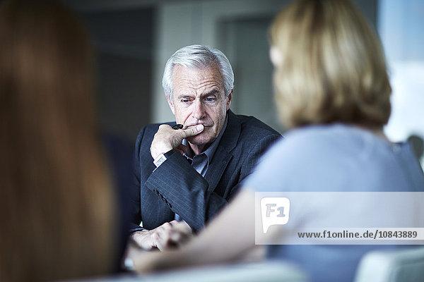 Ein seriöser Geschäftsmann  der in einer Besprechung nach unten schaut.