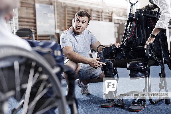 Physiotherapeutin  die dem Menschen im Rollstuhl die Ausrüstung erklärt