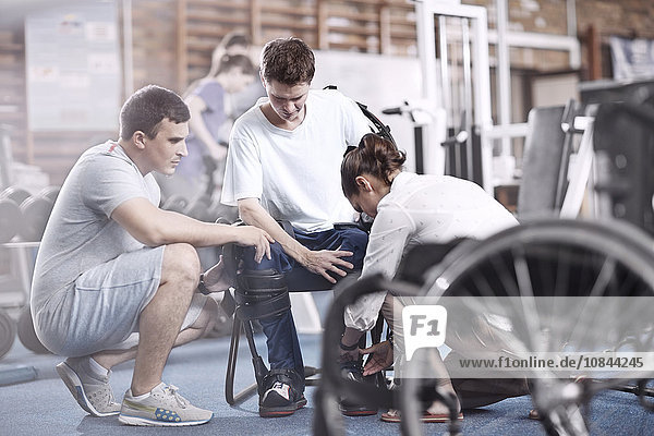 Physical therapists attaching equipment to man