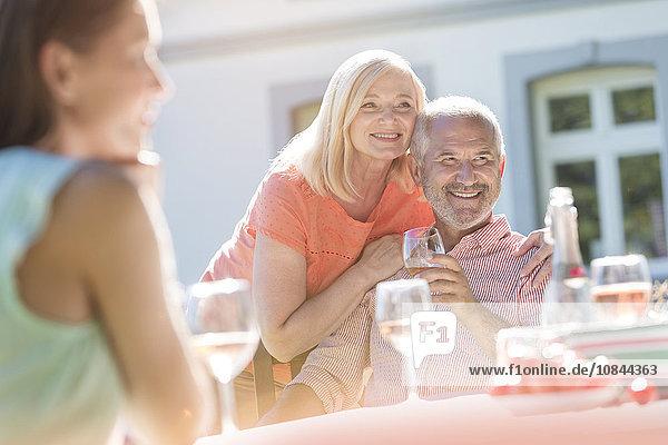 Seniorenpaar lächelt und trinkt Wein auf der Sonnenterrasse