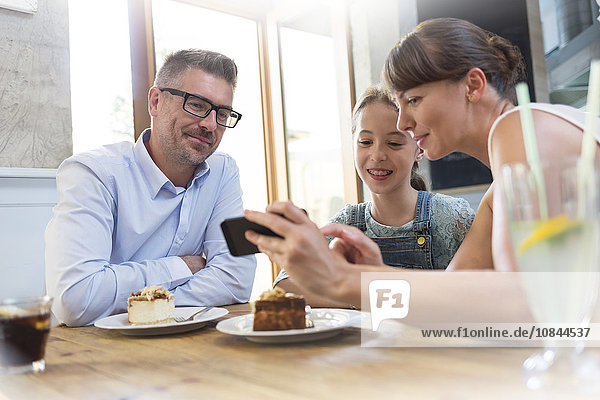 Familie mit Handy beim Dessert am Kaffeetisch