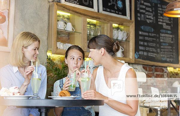 Mutter und Tochter trinken Limonade am Kaffeetisch