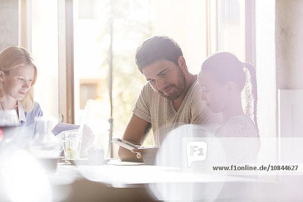 Vater und Tochter mit digitalem Tablett im sonnigen Café