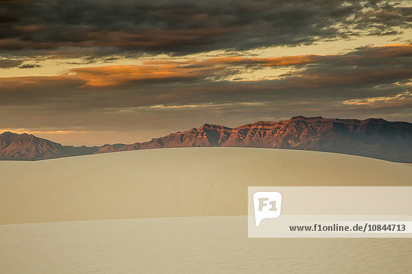 Dramatischer Sonnenuntergangshimmel über Sanddünen und Bergen  White Sands  New Mexico  USA