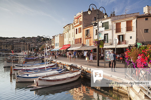 Fishing boats at the harbour  restautants and street cafes on the promenade  Cassis  Provence  Provence-Alpes-Cote d'Azur  Southern France  France  Mediterranean  Europe