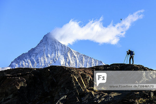 Photographer in action in front of the snowy Weisshorn,  Zermatt,  Valais,  Pennine Alps,  Swiss Alps,  Switzerland,  Europe