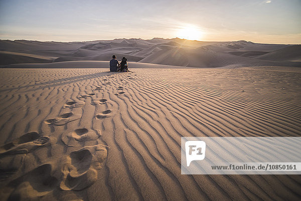 Couple watching the sunset over sand dunes in the desert at Huacachina  Ica Region  Peru  South America