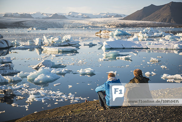 Father and son on holiday at Jokulsarlon Glacier Lagoon at sunset  South East Iceland  Iceland  Polar Regions