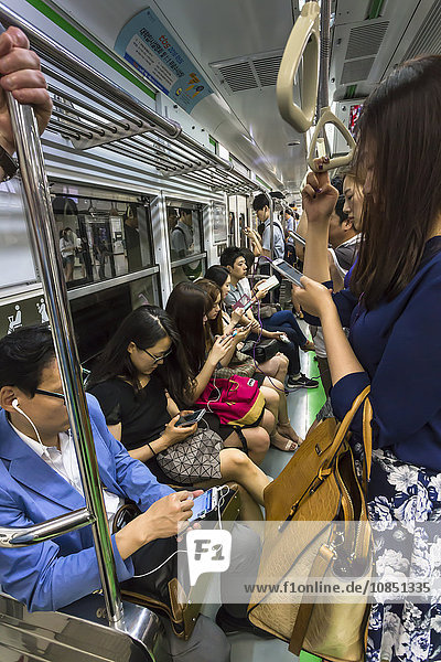 Smartly dressed commuters on the busy subway looking at their phones and e-devices  Seoul  South Korea  Asia