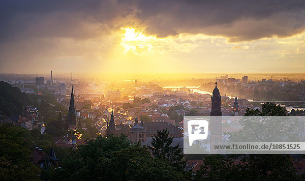 Golden afternoon sun dramatically breaking through rain clouds over the spires of Heidelberg Old Town  Baden-Wurttemberg  Germany  Europe