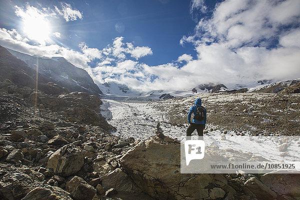 Hiker admires Forni Glacier  Cedec Valley  Stelvio National Park  Valtellina  Lombardy  Italy  Europe
