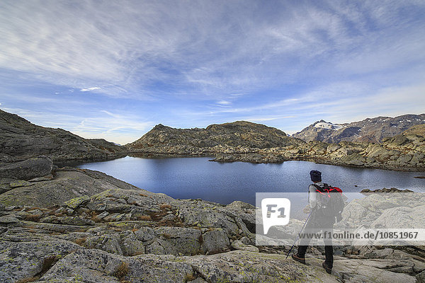 Hiker admires Laghi Azzurri at sunrise  Chiavenna Valley  Spluga Valley  Valtellina  Lombardy  Italy  Europe