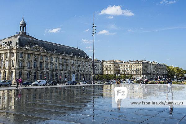 People standing in the water mirror on Place de la Bourse  Bordeaux  Aquiaine  France  Europe
