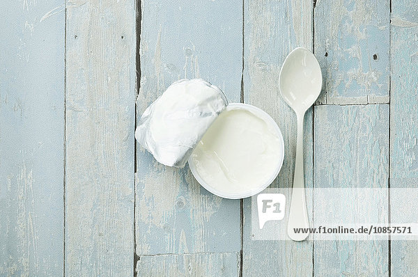 Ein Becher Joghurt mit Löffel auf Holzuntergrund Ein Becher Joghurt mit Löffel auf Holzuntergrund
