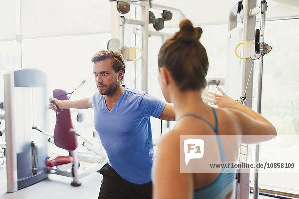 Weiblicher Personal Trainer  der Mann führt  der Kabelbrustfliege an der Gymnastik tut