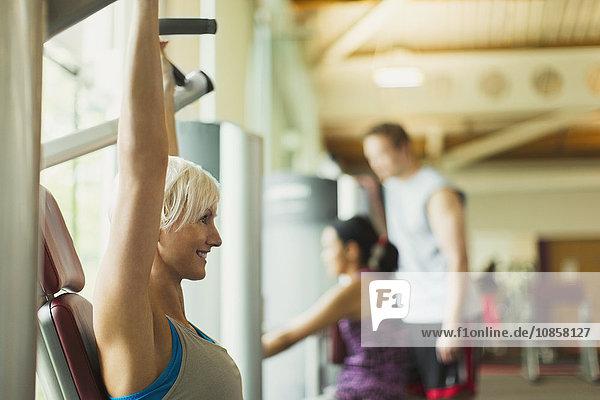 Lächelnde Frau mit erhobenen Armen mit Trainingsgeräten im Fitnessstudio