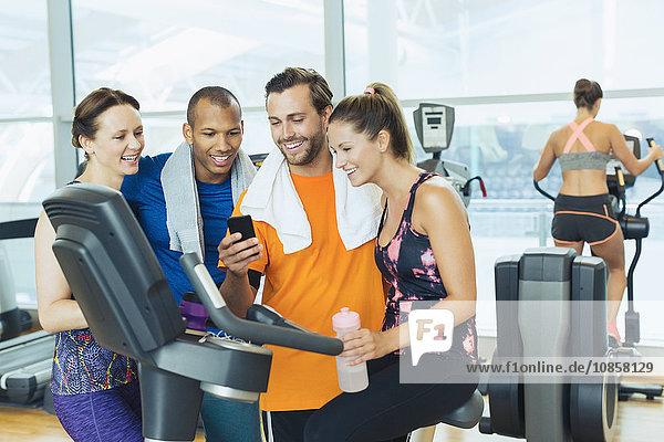 Lächelnde Freunde mit dem Handy am Heimtrainer im Fitnessstudio