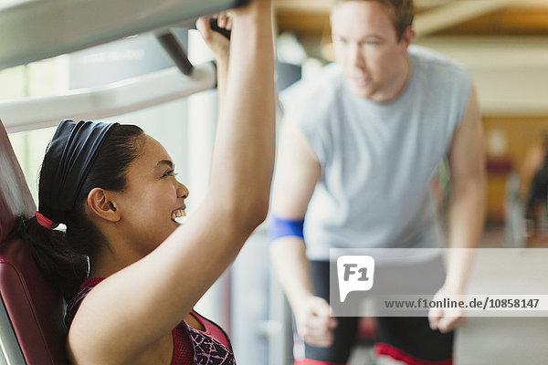 Personal Trainerin  die eine begeisterte Frau mit Trainingsgeräten im Fitnessstudio führt.