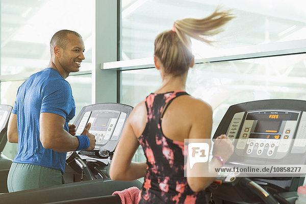 Mann und Frau beim Sprechen und Laufen auf dem Laufband im Fitnessstudio