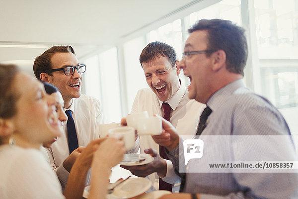 Geschäftsleute lachen und trinken Kaffee im Büro